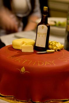 """Wine and Cheese Table""  Moscato Cake filled with mascarpone cheese frosting. Coated and decorated with fondant, gum paste wine bottle, golden grapes, a wheel of fondant cheese, and edible gold."