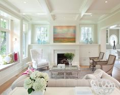The airy living room is framed by the white-enameled coffered ceiling and millwork.