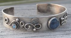 Handmade Sterling Silver cuff with round blue Kyanite cabochon and two small Rainbow Moonstone cabochons among a leaf and Vine motif.. The bracelet is about 1/2 wide and 6 long. It features silver scrolls, leaves, and some granulation detail. In the center is a 10mm natural Kyanite that is bezel set in silver. The rainbow moonstones measure 4mm and 3mm. The cuff has been oxidized to blacken the silver and give it an aged appearance. Fits small to medium sized wrists. One of a kind. Handmade…
