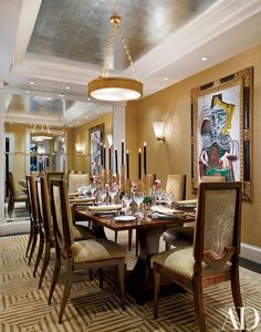 """White cabinetry in the dining room was torn out and replaced with mirrors to create """"a Parisian dining room cocooned in gold silk,"""" Allem says. The painting is by Picasso. Chandelier from Jean Karajian. Tiffany's flatware. Silk wallcovering from Larsen 