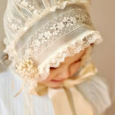This precious bonnet is a modified version of a French bonnet. It is created using a variety of laces from Spanish to English to French Valenciennes laces. The puff is made entirely of lace as is the headband. The bonnet is finished with lace edging. The streamers are made using