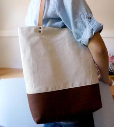 This canvas and leather tote is a wardrobe workhorse—it matches every outfit. With a leather bottom, sturdy leather straps, cotton lining and magnetic closure, this utilitarian handbag will keep your essentials close by. Pack it for your urban commute, for picnics in the park, and especially on global treks. It's not just a bag, it's a companion, in bag form.