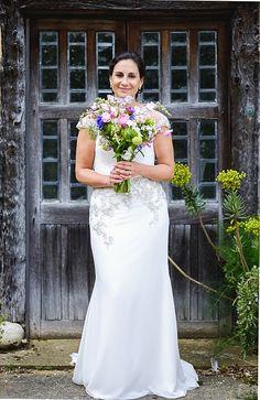 Bride with summer wedding bouquet - English country barn wedding // Warren & Carmen Photography // The Natural Wedding Company