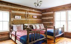Bold buffalo checks—this time in red—resurface on these handmade log beds. Previously bunked, they now better accommodate grown-up guests who visit this rustic and cozy cabin.