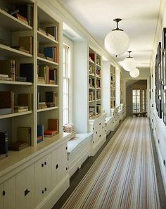 Hallway bookshelves with cabinet storage and benches.