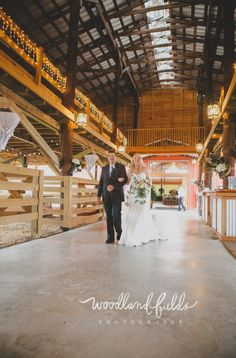 the bride and her dad make their way down the aisle in the barn of the stunning Santa Fe River Ranch
