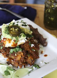Hot TexMess - Huevos Rancheros crossed with Chilaquiles (salsa simmered corn tortillas) topped with avocados, sour cream, candied jalapenos, cheese and more! Gluten free to boot!