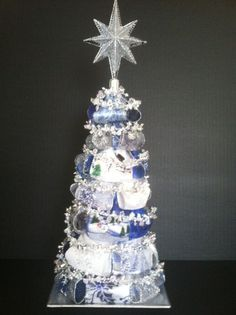 "Saphire Blue, Silver and White Ribbin Tree wrapped with a beaded garland and topped with a silver star. 19""High x 7"" Wide x 7"" Deep. $85"
