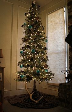 Rustic Christmas tree filled with pine cones and what appears to be an antler underneath it.  House of Turquoise: Merry Christmas!!