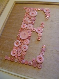 Personalized Vintage Style Nursery Letter Art -- Pink Buttons on Antique White Silk -- Ready To Frame in 8x10 Frame (frame not included). $60.00, via Etsy.