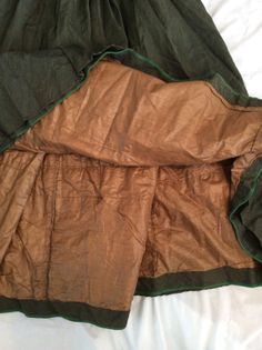 Inside of the matching 1860s skirt, showing the polished cotton lining and bound skirt edge.