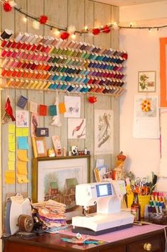 How I would love to have a sewing space in my craft room just like this (complete with the rainbow of thread spools!)