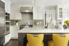 Gray and white kitchen with yellow accents boasts a gray island seating canary yellow counter stools in front of a honed white marble countertop finished with a stainless steel apron sink and a polished nickel gooseneck faucet.