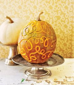 """Achieve enchanting effects by scoring the skin of a pumpkin with motifs taken from your home's décor. The curlicues here were inspired by the """"Vermicelli"""" wallpaper from Farrow & Ball. The flesh was scooped out from an opening cut in the bottom, then the motif was inscribed with a linoleum cutter.   - CountryLiving.com"""