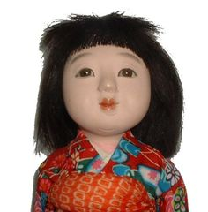 11 inch Japanese Doll    The 11 inch doll depicts a Japanese girl. She has composition head, body, hands and feet and glass eyes. I believe she also have a gofun finish and real hair. She is wrapped in paper, under her kimono, which feels like cotton.