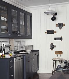 """Our family and friends visit us here often,"" Thiergartner says, ""and they all have such fun, colorful personalities. I went with a mostly black-and-white palette so the house can serve as a background, letting people shine instead."" In this photo: Honed black granite countertops and black-painted oak cabinets offer a dramatic counterpoint to the kitchen's white plank walls. Thiergartner bought the cabinet doors' nautical latches at a marine hardware store.  Bright idea: Plumbing-pipe…"