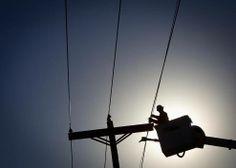 An electrical line technician works on restoring power after a tornado in Vilonia, Arkansas.