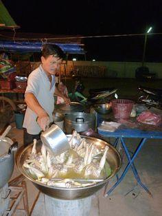 Stewing chicken parts at the night market in Vientiane Laos