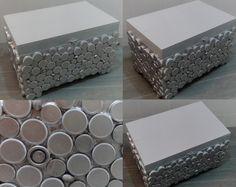Caixa de madeira, lacada a cinza e forrada com tampas de plástico pintadas de prata.