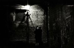 1936. A couple under a lamp post at De Nes near Langebrugsteeg in Amsterdam. Nes is a narrow street in the center of Amsterdam. It runs parallel to and to the east of Rokin. In the early 1800's, Nes became a center for entertainment. Its attractions included brothels, café-chantants and artists' cafés. By the 1960s, Nes had become known as a theatrical quarter with sites including Frascati, Engelenbak and De Brakke Grond. Stadsardhief Amsterdam / E. van Moerkerken. #amsterdam #1950 #Nes