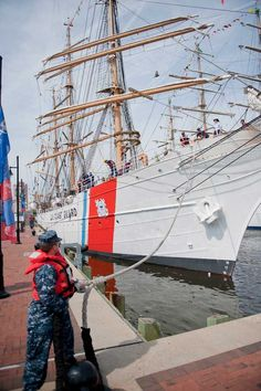 A sailor from the US Navy helps crewmembers aboard the Coast Guard Cutter Eagle, a 295-foot barque homeported in New London, Conn., depart after participating in Operation Sail 2012 in Norfolk, Va. OpSail 2012 Virginia is commemorating the bicentennial of the War of 1812 in hopes to inspire patriotism and foster interest in American maritime history and heritage. (Photo by Petty Officer 2nd Class Walter Shinn)