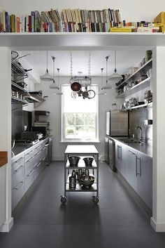 London architecture and design firm Project Orange designed a commercial galley kitchen for a couple who run a monthly dining club out of their home. A stainless steel cart on casters serves as a moveable island. Photograph via Project Orange.