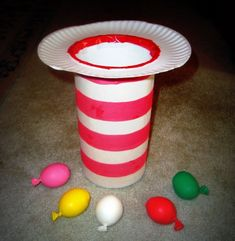 Cat in the Hat toss game  Glue white construction paper to the outside of the oatmeal container.  You can use small balls or beanbags for this Cat in the Hat toss.  I made some homemade balloon balls by putting Moon Dough into balloons.  They're squishy, yet solid.  It was a nice sensory addition to this activity.