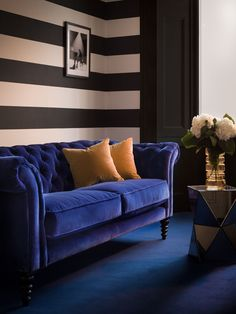 Beautiful dark and dreamy interior inspiration. A dark blue velvet sofa, black and white striped walls, and dark carpet is perfect for a moody living room.
