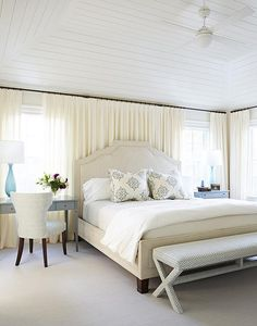Ivory and gray bedroom features an ivory bed dressed in white and blue bedding, with ivory curtains behind bed, flanked by a gray desk as nightstand to the left and a gray chest as nightstand to the right illuminated by turquoise blue glass lamps.
