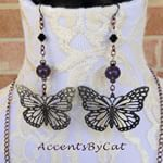 Antiqued silver butterfly earrings. These earrings are made with copper chain, purple glass beads and black Swarovski crystal beads. They dangle 3 and a half inches from the top of the nickel free hooks. $18 + shipping To buy click the link in bio.