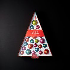 A tree and ornament advent calendar with 25 reusable tin ornaments containing sweet treats. Includes one $5 Starbucks Card.