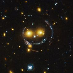 "In the center of this image, taken with the Hubble Space Telescope, are two faint galaxies that seem to be smiling. In the case of this ""happy face"", the two eyes are the galaxies SDSSCGB 8842.3 and SDSSCGB 8842.4 - Image Credit: NASA and ESA -  Image enhancement: Jean-Baptiste Faure"