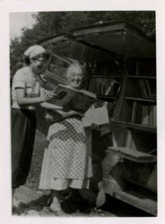 Watauga County Library bookmobile in Sands, rear view with librarian and library board member laughing and looking at book ^cs