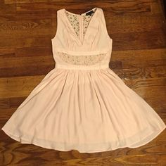 Light pink mini dress with beautiful panels Size Small light pink dress. Never worn, ordered online and is SO cute, but too short for me! (I am 5'11..) Zips up the back. Has embroidered lacey panel across the front and on the back with a pleated skirt. Would be very cute with some wedge heels! 100% polyester. Lovposh Dresses Mini