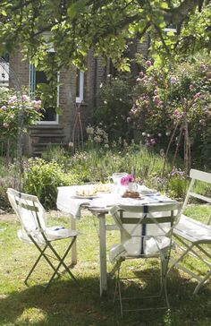 Jane sets the table under an old apple tree in her garden, which includes a mix of flowers and edible herbs such as rosemary, mint, lemon balm, fennel, marjoram, and chives.