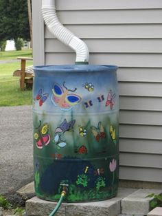 hand painted rain barrel with a little graphic photo that shows how a rain barrel works and link to rainfall harvest calculator