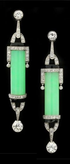 A pair of Art Deco platinum, diamond, onyx and jade earrings, circa 1925. Each vertically set with a central barrel shaped green jade, mounted to top and bottom with borders and stirrup shaped forms flanking horizontal bands of onyx and set with round eight cut diamonds, and a round old cut diamond set to top and bottom. #ArtDeco #earrings