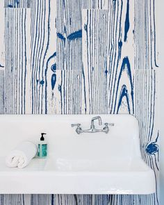 White-and-blue wood-grain-patterned UonUon tiles by 14oraitaliana line the bathroom walls in a loft above the garage in a Rhode Island summer cottage. Photo by Brian W. Ferry #bathroom by dwellmagazine