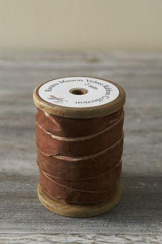 A spool of brown velvet ribbon