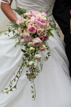 An exquisitely traditional English cascading wedding bouquet of Lily of the Valley, English Garden Roses, Miranda and pink Sarah Bernhardt Peonies