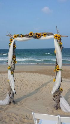 #simplysugarsnap #sugarsnapevents #OBXWeddings #beachwedding #driftwood #weddingarch  Our driftwood arch adorned with ivory fabric and Sunflowers.