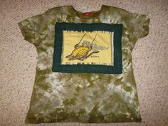 T-shirt image of Kliban's Cat on a Swing framed with eyelet lace and stitched to a tie-dyed shirt.