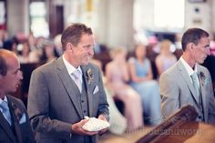 Best man smiles with wedding rings on pillow at Swanage church wedding ceremony.  Photography by one thousand words wedding photographers