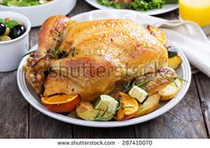Whole roasted chicken with potatoes on dinner table