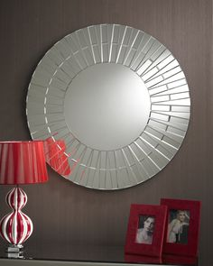 This impressive round mirror features a plain central hub while the border has an effect like a set of ridged spokes made of clear bevelled glass sections. The is a line through the border giving it a double effect. http://www.chicconcept.co.uk/art-deco-mirrors/1822-art-deco-eclipse-mirror-5055157622334.html