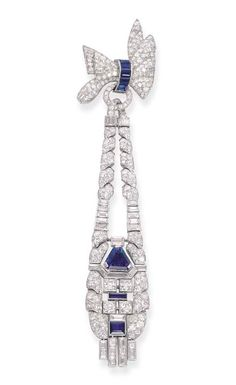 AN ART DECO DIAMOND AND SAPPHIRE PENDENT BROOCH   The pavé-set diamond bow with rectangular-cut sapphire detail suspending a circular and baguette-cut diamond pendant with central triangular, rectangular and square-cut sapphire collets to the baguette-cut diamond fringe, circa 1935, 15.0 cm. long, with French assay mark for platinum, no. K5874