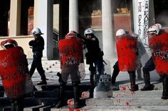 Riot police stand guard with red paint on their shields, thrown by anti-establishment protesters during a demonstration against high security prisons in Athens. (Alkis Konstantinidis/Reuters)