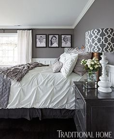 "Walls in ""Silver Cufflink"" by Ralph Lauren give this bedroom a luxe, glamorous feel that's embellished with piles of soft bedding and pillows. Liberal doses of white on fabrics and wainscoting balance the dramatic grays."