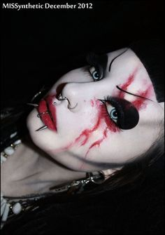Cyber style black makeup with blue contact lens lips and septum piercing.