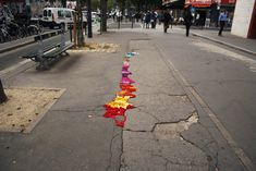 """Project Pothole""  Artist Juliana Santacruz Herrera has taken to the streets of Paris to repair unsightly potholes and cracks with braids of colorful yarn.  How cool."